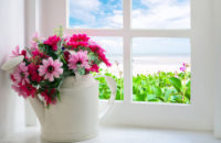 Bouquet of artificial flowers in a window to look through the window at the sea. relaxation concept